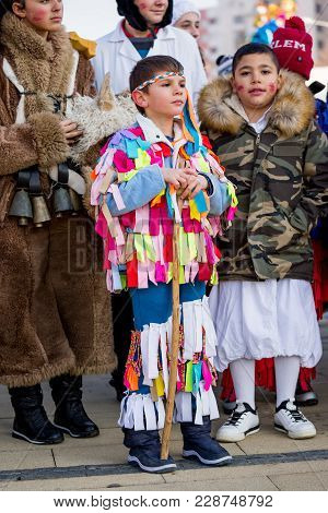 Pernik, Bulgaria - January 26, 2018: Young Male Participant In Colorful Rag Kuker Costume Leans On W