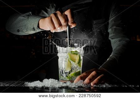 Bartender Hand Holding A Glass Of Splashing Caipirinha Cocktail On The Bar Counter Against Dark Back