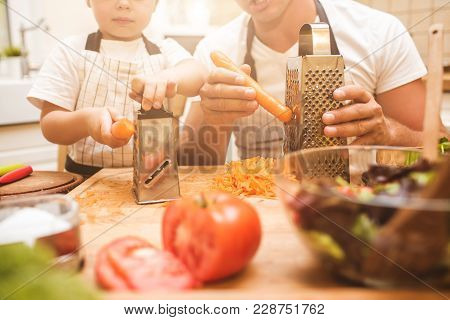 Young Dad Prepares Food With His Little Son. The Family Rubs Carrots In A Light Kitchen.