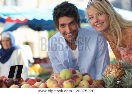 Young couple at a fruit stall in a market