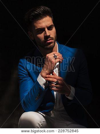 seated elegant man wearing rings is  dreaming away in studio
