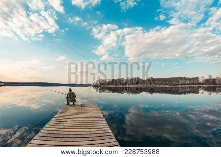 Alone Fisherman Sitting On The Pier Far Out Into The Lake, The Weather Is Calm