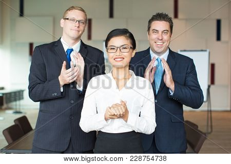 Portrait Of Successful Young Asian Female Leader Wearing Glasses And Her Caucasian Male Executives A