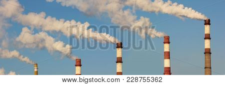 Factory Pipes With Clubs Of White Dense Smoke Or Steam Against The Blue Sky, Panorama. Environmental