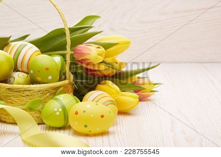 Colored easter eggs in the basket, spring tulips flowers and ribbon on wooden background. Greeting card.