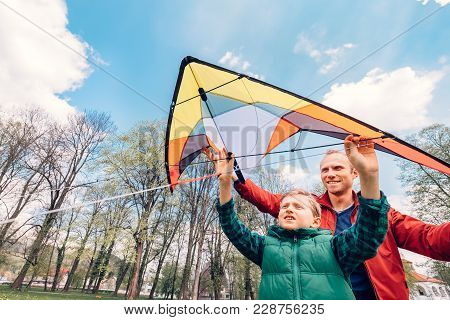 Father And Son Start To Fly A Kite In Sky