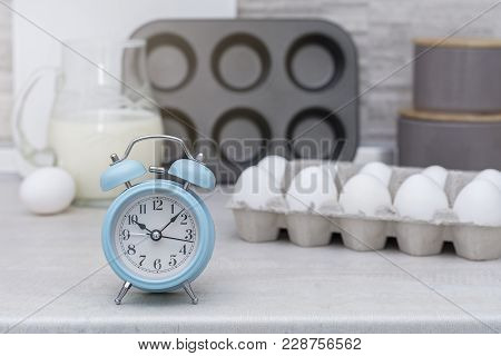 Light Big Kitchen. Tableware For Cooking, Cake Mold And Tray With Eggs On The Table. Blue Alarm Cloc
