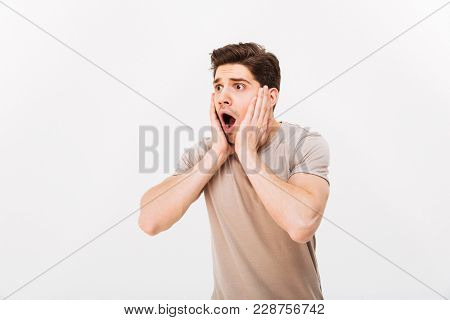 Photo of young man in horror grabbing his face and screaming while looking aside isolated over white background