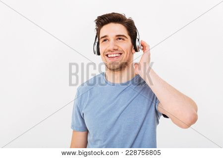 Photo of adult smiling guy with short dark hair listening to music via headphones isolated over white background