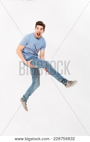 Full-length photo of amusing guy in casual t-shirt and jeans holding leg like playing guitar isolated over white background