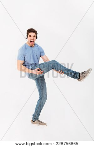 Full-length photo of joyous guy listening to music via headphones and holding leg like playing guitar isolated over white background