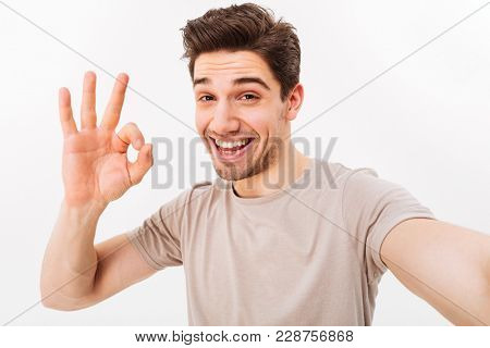 Cheerful man in casual t-shirt and bristle on face smiling on camera with alright sign while taking selfie isolated over white background
