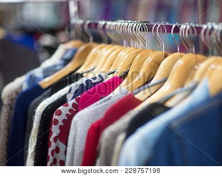 Beautiful Clothes For Winter Autumn Season. Merchandise In A Shop. Fashionable Clothes On Hangers In