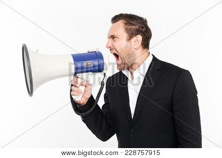 Horizontal portrait of tense male employer in business suit shouting in loudspeaker full of anger isolated over white background