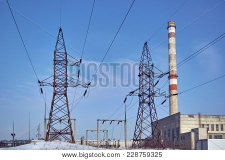 Supports High Voltage Transmission Lines And Pipe Thermal Power Station. In The Background Is A Clea