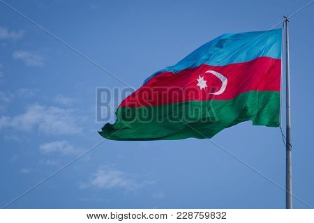 The National Flag Of Azerbaijan On The Background Of Blue Sky . Azerbaijan Flag Waving In The Wind A