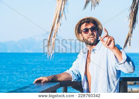 Young Handsome Man Ordering At The Beach Bar
