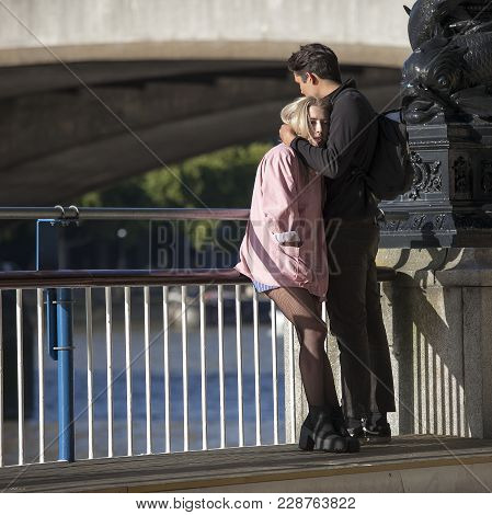 London, England - September 11, 2017 The Boy Hugs The Girl In A Pink Jacket, Leaning On The Railing