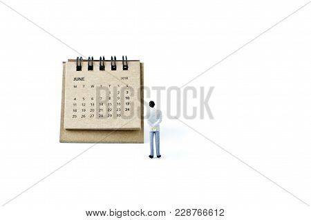June. Two Thousand Eighteen Year Calendar And Miniature Plastic Man On White Background.