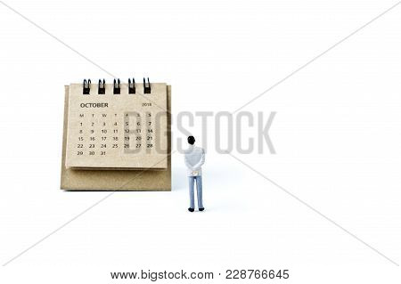 October. Two Thousand Eighteen Year Calendar And Miniature Plastic Man On White Background.