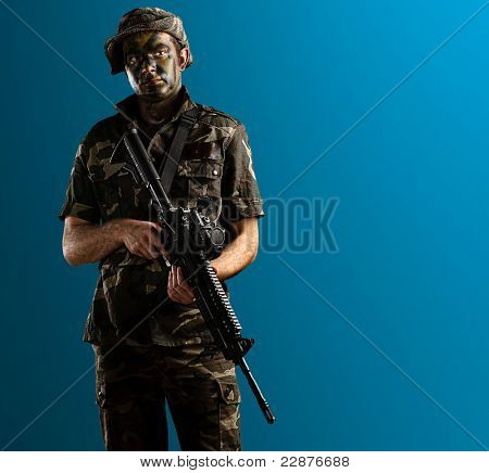 young soldier with jungle camouflage on a blue background