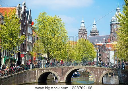Amsterdam, Netherlands - April 20, 2017: Bridge, Canal And St. Nicolas Church In Amsterdam. Amsterda