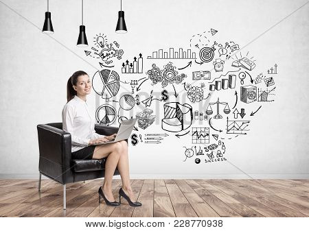 Charming Young Businesswoman Sitting In An Armchair In A Room With Concrete Walls And Business Strat