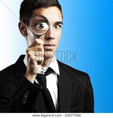 portrait of young man with a magnifying glass on blue background