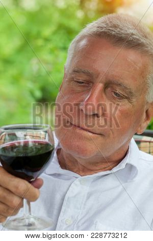 Mature handsome man with a glass of wine