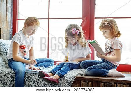 Three Children Read, Draw And Write. A Group Of Children Is Studying. The Concept Is Childhood, Lear