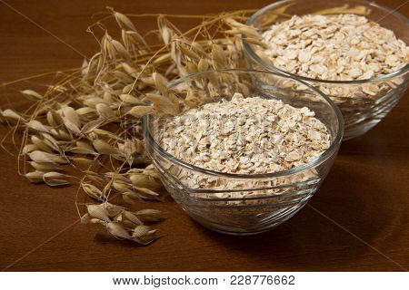 Oat Ears Stems And Oat Flakes In A Bowl On A Dark Brown Wood Background. Oat Flakes Big And Small Si
