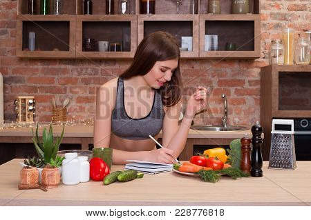Health Is Wealth! Young Appealing Smiling Lady Is Surrounded By Salubrious Vegetables Sits At The Ki