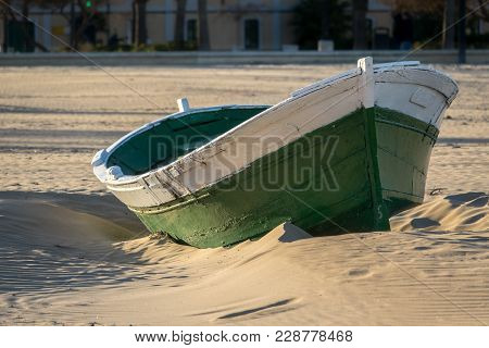 Wrecked Wooden Fisher Boat. Boat Stranded In The Sand Of A Beach Broken Abandoned Boat In Sand