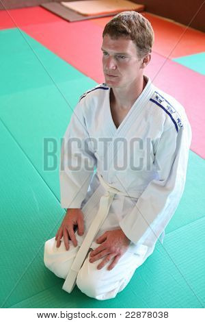 Kneeling man on judo mat