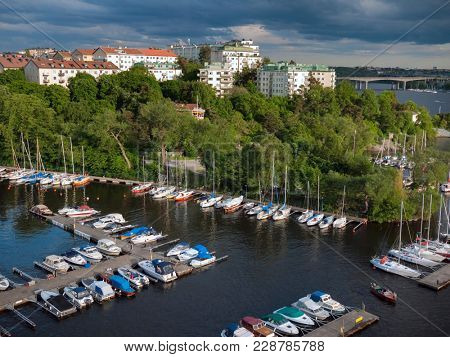 Stockholm Sweden. View of Kungsholmen island from huge Vasterbron bridge. Yachts in marina.