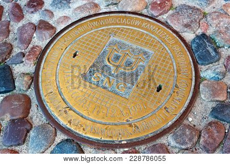 Gdansk, Poland - June 07, 2014: Yellow Sewer Manhole On Cobblestone In The Historical Part Of Gdansk