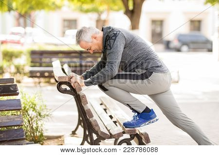 Hispanic Middle Aged Man Stretching On Park Bench