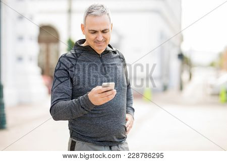 Good Looking Mature Man Texting On His Mobile Phone Outdoors After Working Out In The City