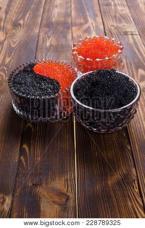 fresh raw red salmon caviar with black sturgeon caviar in white crystal bowls on burned vintage wooden table background