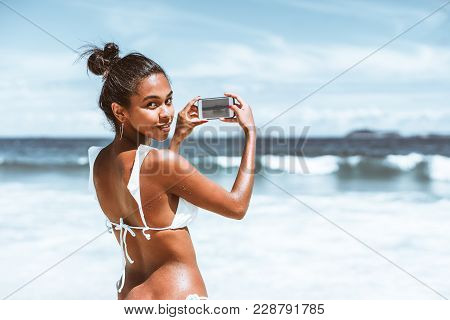 Rear View Of Svelte Young Brazilian Girl In Swimsuit With Wet Skin, Half-turned And Looking At Camer