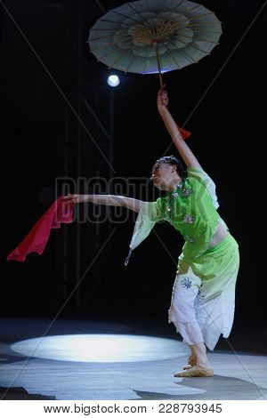 SAINT-PETERSBURG, RUSSIA - FEBRUARY 6, 2018: Lee Jing-Jing performs the dance with umbrella during the Dance festival of young people of China and Russia. Six choreographic groups take part in event