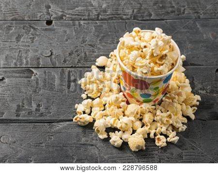 Popcorn Is Poured From A Multi-colored Paper Cup On A Rustic Table. Vegetarian Food From Corn.