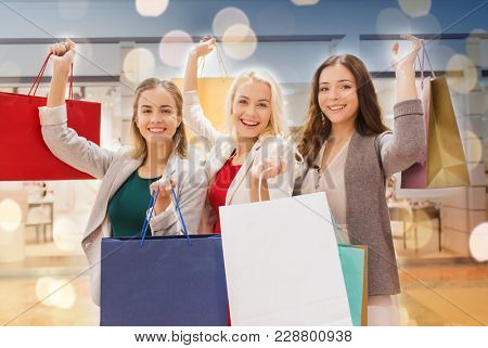 sale, consumerism and people concept - happy young women raising hands with shopping bags in mall