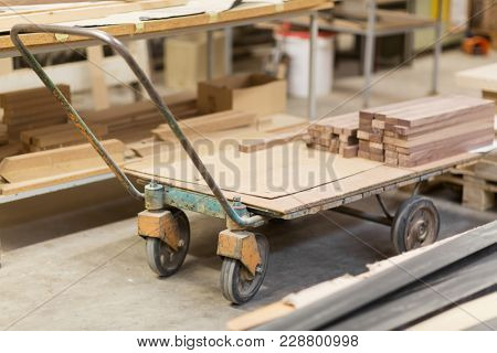 production, manufacture and woodworking industry concept - boards on old loader at furniture factory workshop