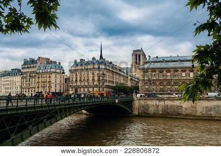 PARIS, FRANCE - MAY 24, 2016: People o the bridge over Seine river and typical parisian buildings on background in Paris -  capital and most populous city in France, popular tourist destination.