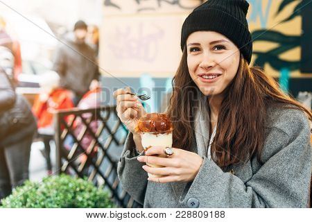 Happy Girl Eating Dessert In A Cafe And Smiling. Outside. In The Autumn.
