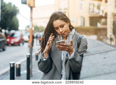 Portrait Of Beautiful Young Woman Using Her Mobile Phone In The Street.