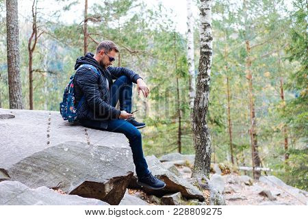 Guy Sits In The Woods On A Rock And Makes A Selfie