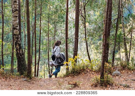 The Girl Walks Along The Path In The Woods