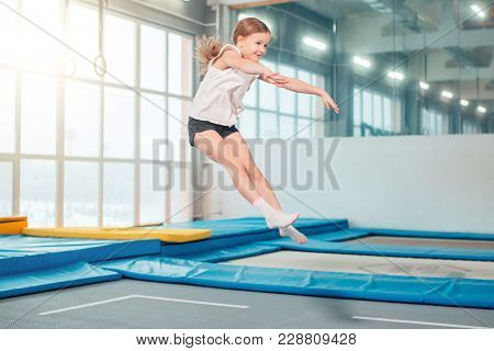Girl Jumping High In Striped Tights On Big Trampoline.